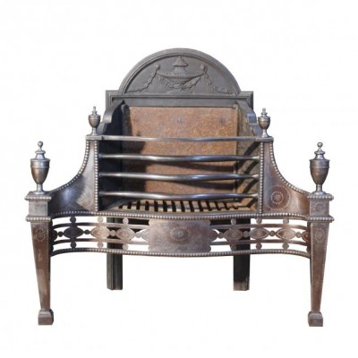 An antique fire grate with pierced steel fret and urn finials