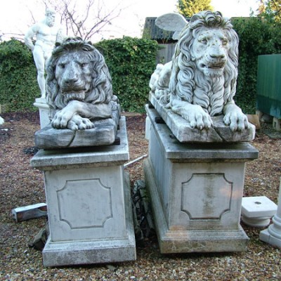 Aged Lions statues on plinths (pair)