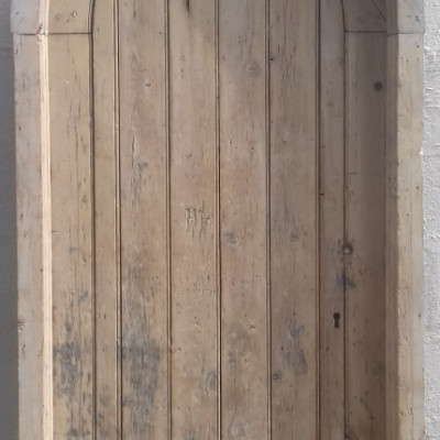 A Victorian arched church door with frame.
