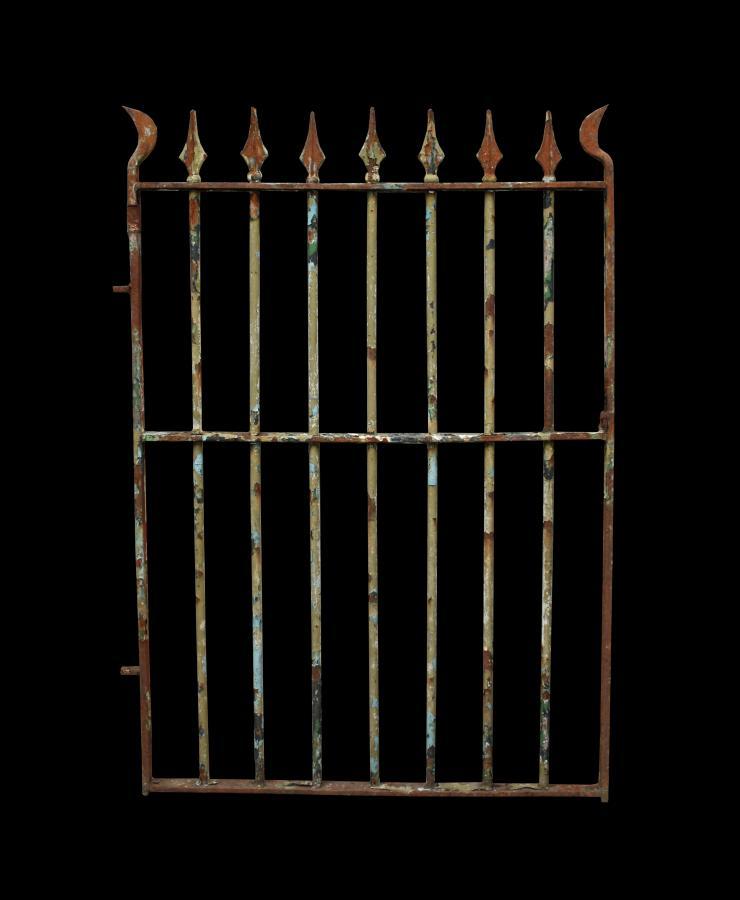 An antique wrought iron pedestrian / side gate
