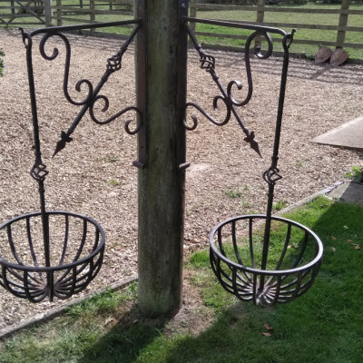 Pair of beautiful wrought iron hanging baskets with decorative brackets