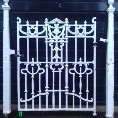 An Art Nouveau cast iron pedestrian gate with its original posts and sections of railing.