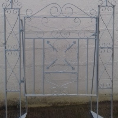 A reclaimed wrought iron garden gate with posts.