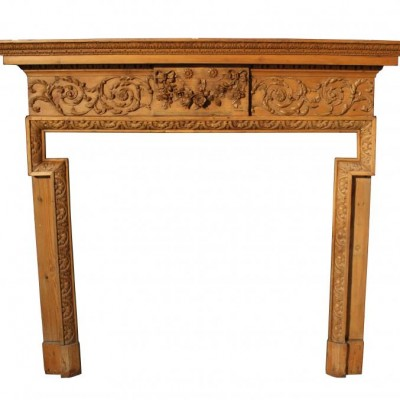A large early 19th C carved pine fire surround