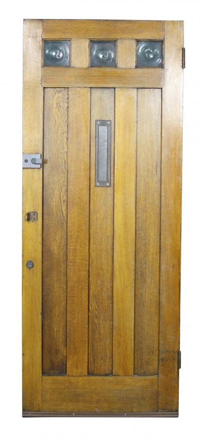 An early 20th Century oak front door with bull's-eye glass