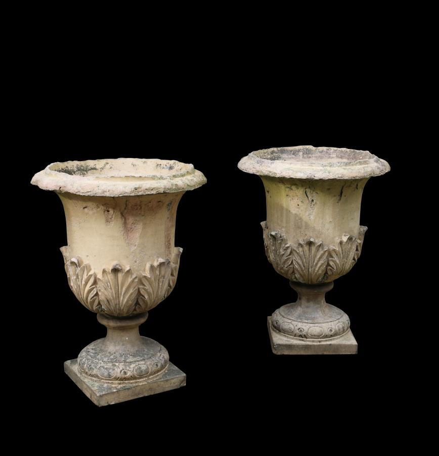 A pair of weathered early 20thC garden urns