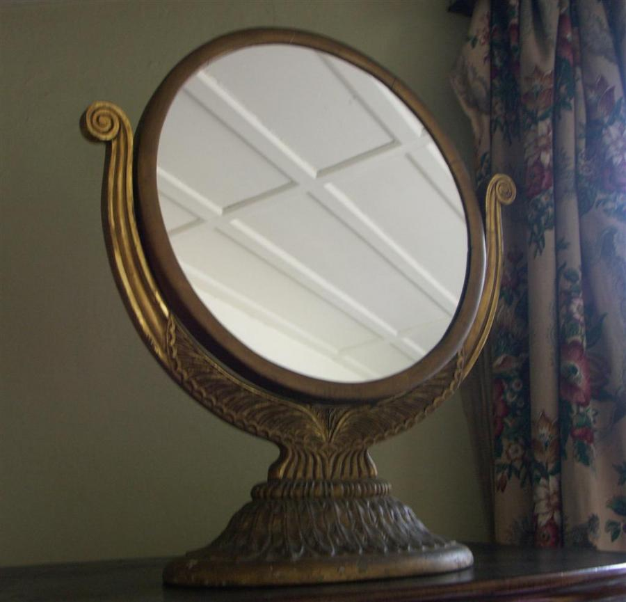 circular mirror on carved stand