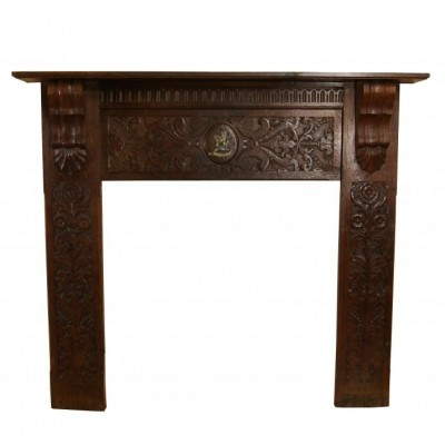 A late Victorian carved oak fire surround